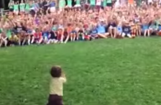 Toddler adorably conducts cheering crowd