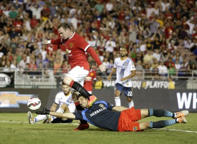 Manchester United's Wayne Rooney, top, scores past Los Angeles Galaxy goalkeeper Jaime Penedo.