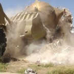 A bulldozer destroys a monument called