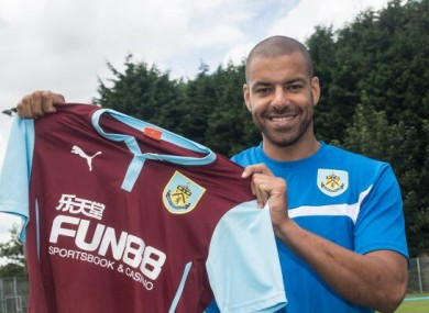 Reid holds up the Burnley jersey.