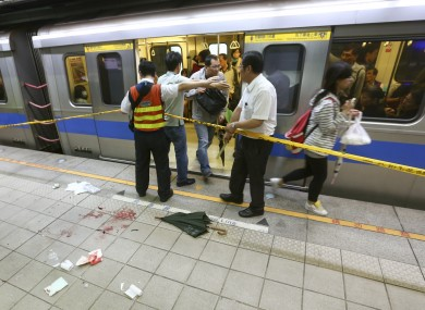 File photo dated 21/5/14 showing officials blocking parts of the knife attack scene at a subway platform in Taipei, Taiwan.