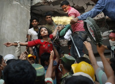 A Bangladeshi woman survivor is lifted out of the rubble by rescuers after the collapse of Rana Plaza.