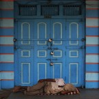 A man sleeps in front of a closed shop in Hyderabad, India.<span class=