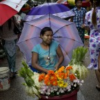 A street flower seller sits in the middle of a street market as the rain eases in Yangon, Myanmar.<span class=