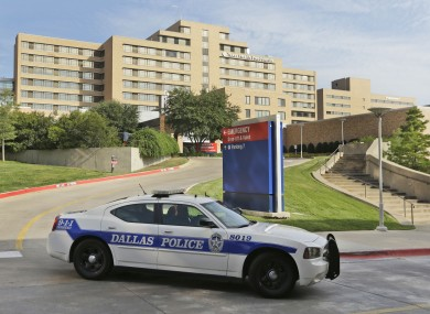 A police car drives past the entrance to the Texas Health Presbyterian Hospital in Dallas.