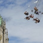 People ride a merry-go-round in front of St. Paul church at the 181st Oktoberfest beer festival in Munich, southern Germany.<span class=
