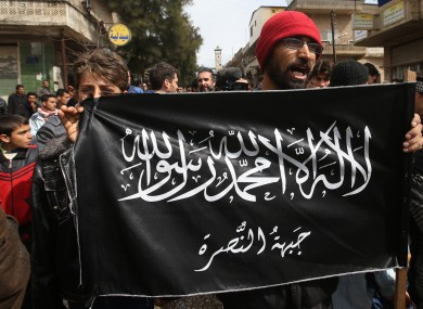 In this file photo, anti-Syrian President Bashar Assad protesters hold the al-Nusra flag.