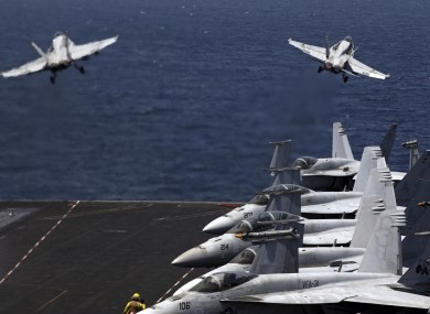 U.S. F/A-18 fighter jets take off for a mission in Iraq from the flight deck of an aircraft carrier in the Persian Gulf.