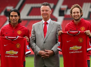 Manchester United manager Louis van Gaal (centre) with his new signings Radamel Falcao (left) and Daley Blind during a photocall at Old Trafford today.