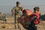 Turkish soldiers stand guard as a Syrian refugee boy carries his belongings at the border in Suruc, Turkey