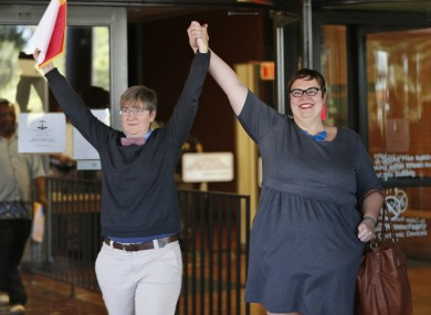 Nicole Pries, left, and Lindsey Oliver hold up their marriage license as they celebrate being one of the first same-sex couples in Virginia to be married outside a Richmond Court building.