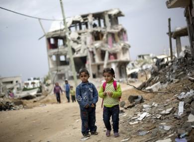 Palestinian school children walk through destroyed houses in Gaza City's Shijaiyah neighborhood last Sunday.
