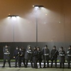St Louis police officers stand their post in the parking lot of a gas station as protesters march through the streets of St Louis protesting against recent shootings of young black men by law enforcement officers. (AP Photo/Charles Rex Arbogast)<span class=