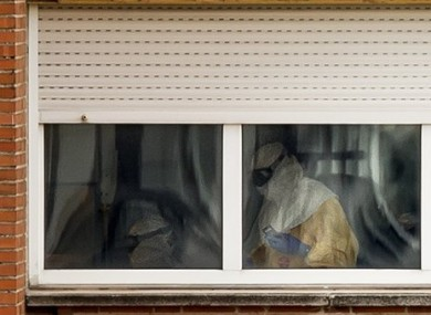 Medical practitioners wearing protective clothing are seen attending a patient inside an isolated ward on the sixth floor of the the Carlos III hospital in Madrid.