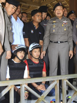 The two suspects, named as Saw (L) and Win (R), are paraded by Thai police.