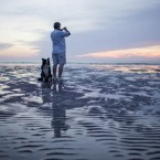 A man walking his dog on the beach stops to take a picture of the sunset in Montevideo, Uruguay. (AP Photo/Natacha Pisarenko)<span class=