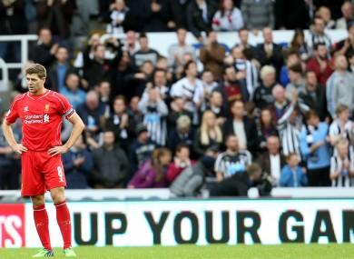 Liverpool's captain Steven Gerrard stands dejected as Newcastle United's Ayoze Perez celebrates earlier.