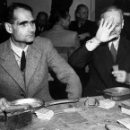 Former Deputy Fuhrer Rudolf Hess and former German Foreign Minister Joachim von Ribbentrop (covering his face) eating a meal under guard at the Nuremberg Court House <span class=
