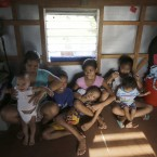Typhoon survivor Agnes Bacsal poses with her children, from left, John William, Jobani, Jonathan Jr., Maria Jean, Maria Joy, and Maria Rose, inside their crudely reconstructed home in Tacloban.<span class=