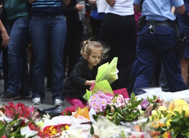 A girl lays flowers in a makeshift memorial near the cafe where the hostages were held.