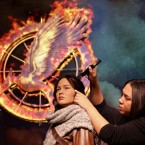Hair stylist Gemma Sim puts the finishing touches to a new wax figure of The Hunger Games' Katniss Everdeen, played in the film by Jennifer Lawrence, at Madame Tussauds in London.<span class=