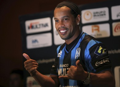 Brazil's Ronaldinho poses for a photo after slipping on his new Queretaro soccer club jersey at a press conference in Mexico City last September.