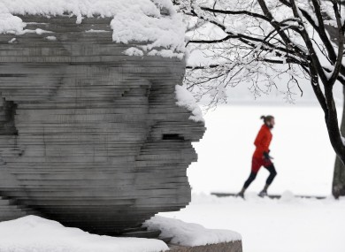 A jogger passes a statue of Arthur Fiedler on the Esplanade in Boston on Saturday.