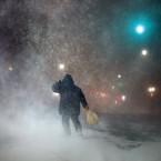 A man battles fierce headwinds as he walks on Congress Street in Portland, Maine, during a blizzard.<span class=