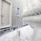 Frozen sea spray coats houses the day after a winter storm in Scituate, Mass. Residents of Massachusetts woke up on Wednesday to cars buried in several feet of snow, and secondary roads that remain covered. <span class=