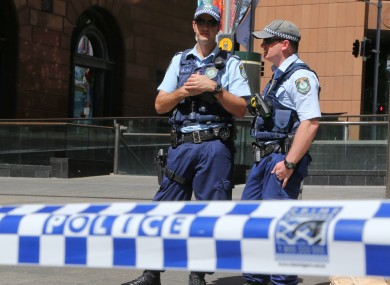 Police stand near a police line to stop pedestrian access close to a cafe under siege at Martin Place in Sydney in December.