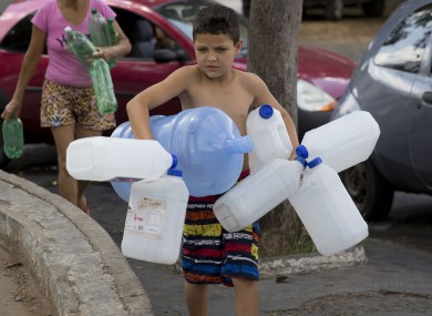 A boy carrys water containers in Brazil.