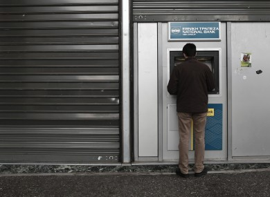 A man uses an ATM outside a National Bank branch in central Athens.