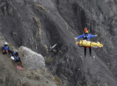 A rescue worker is lifted into an helicopter at the crash site.