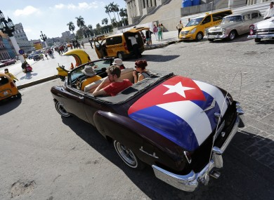 Tourists take a ride in a classic convertible in Havana.