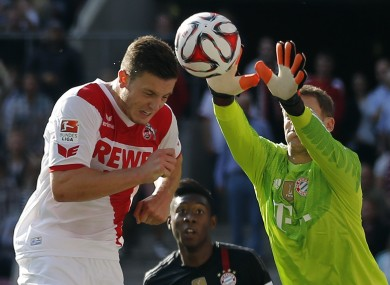 Wimmer challenges Bayern goalkeeper Manuel Neuer for the ball.