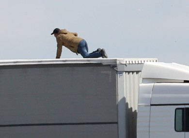 File photo of a man trying to board a lorry