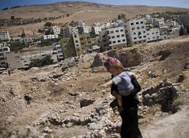 A Palestinian woman carries her baby in the city of Nablus near where the attack took place.