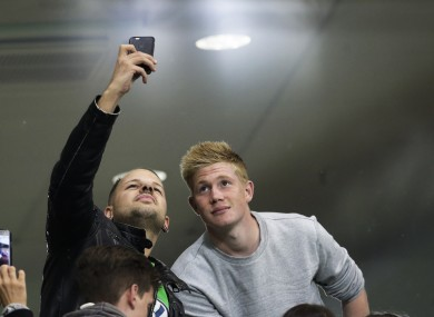 Wolfsburg's Kevin De Bruyne, right, poses for photos with people on the tribune during half time of the German Bundesliga soccer match between Vfl Wolfsburg and FC Schalke 04.