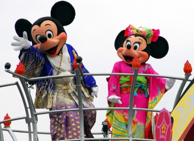 Mickey and Minnie Mouse clad in traditional Japanese kimonos greet visitors during a New Year celebration at Tokyo Disneyland.