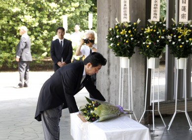 Japannese PM Shinzo Abe laying a bouquet of flowers for those that died during World War II