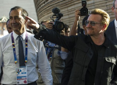 Bono waves as he arrives for a visit to Expo 2015 in Milan.