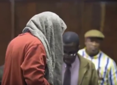 The man covers his face as he appears in court.