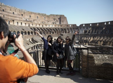Tourists pose for a happy snap at Rome's Colosseum