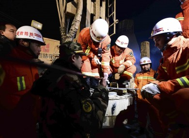 Rescuers try to contact the trapped people at a collapsed mine in Pingyi County, east China's Shandong Province