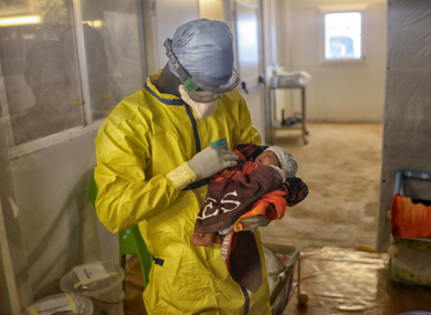 An MSF health worker holds baby Nubia Souma, the last known Ebola patient in Guinea.