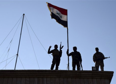 Iraqi soldiers plant the national flag over a government building in Ramadi.