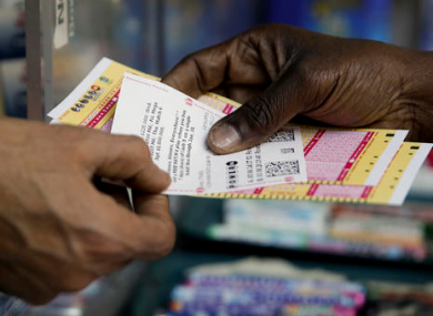 A person purchase Powerball lottery tickets from a newsstand in Philadelphia.