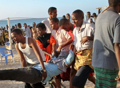Relatives carry away a dead body from the beach following an overnight attack on a beachfront restaurant in Mogadishu, Somalia.