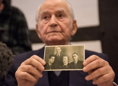 Concentration camp survivor Leon Schwarzbaum presents an old photo showing himself, left, next to his uncle and parents, who all died in Auschwitz, during a press conference.
