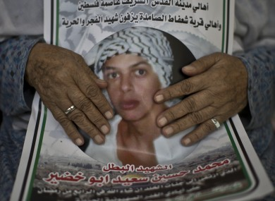 Fatimah Abu Khdeir, 85, grandmother of 16-year-old Mohammed Abu Khdeir holds a poster featuring a  photo of him.